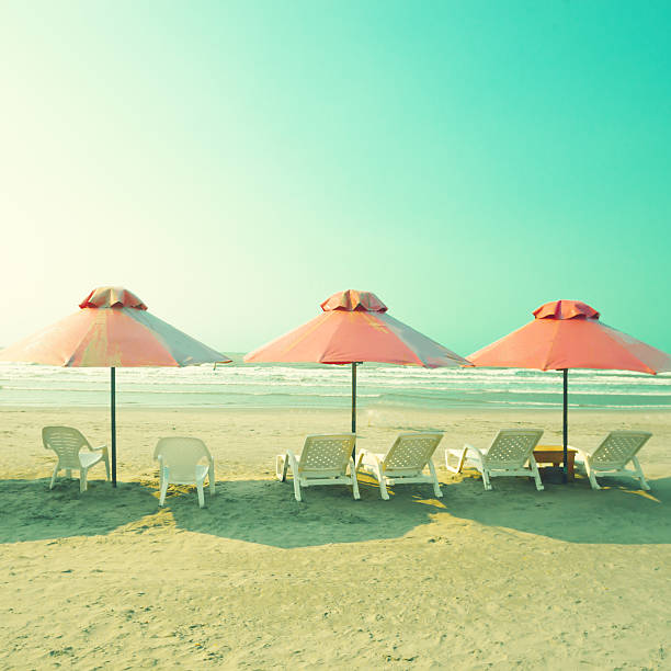 Pink Umbrellas in the beach stock photo