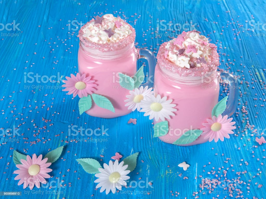 Pink unicorn milk shake with whipped cream, sugar and sprinkles, set on a blue wooden board stock photo