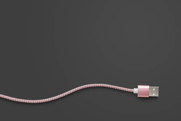 Pink USB cable on dark grey with clipping path stock photo