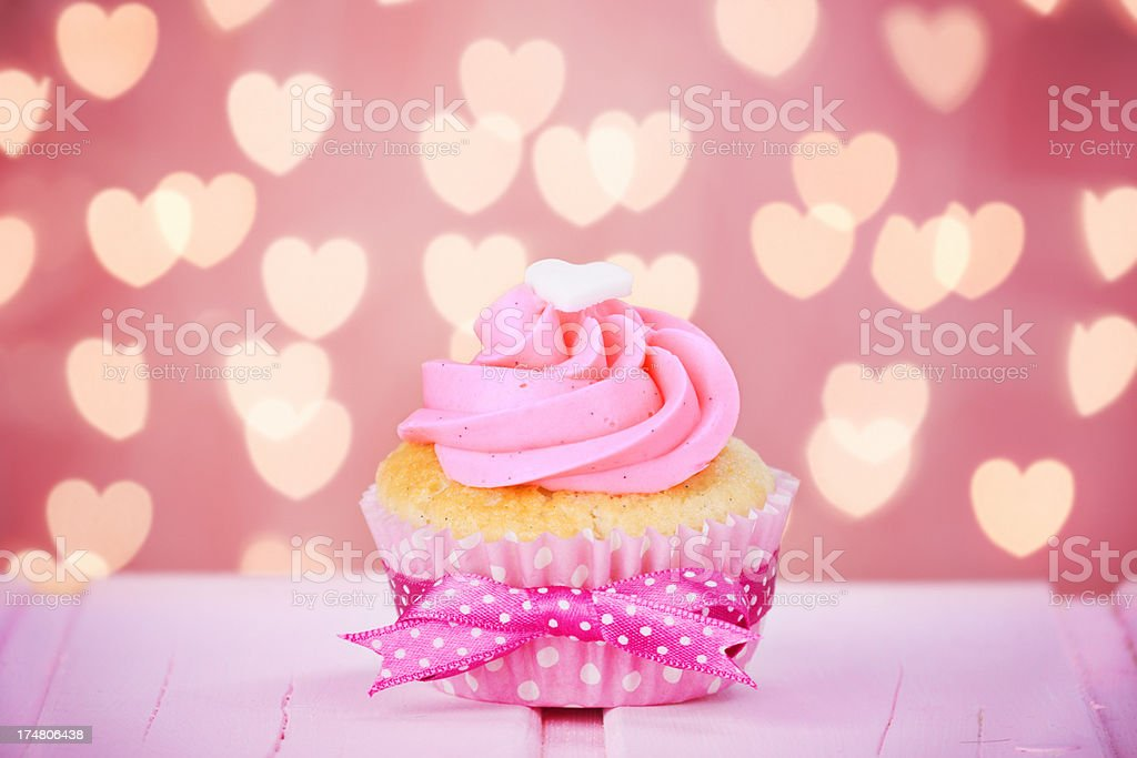 Pink Valentine cupcake on a rustic pink table royalty-free stock photo