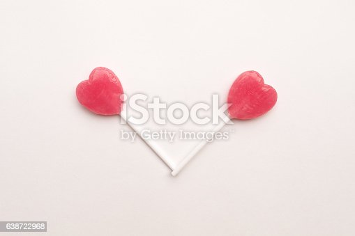 157527860 istock photo Pink Valentine's heart shape lollipop candy empty pastel white background 638722968