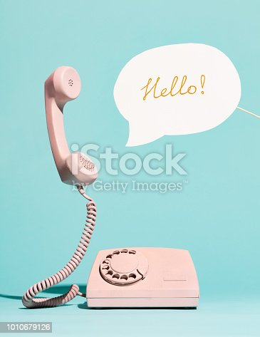 Pink vintage phone and speech bubble saying HELLO. Call center, conversation.