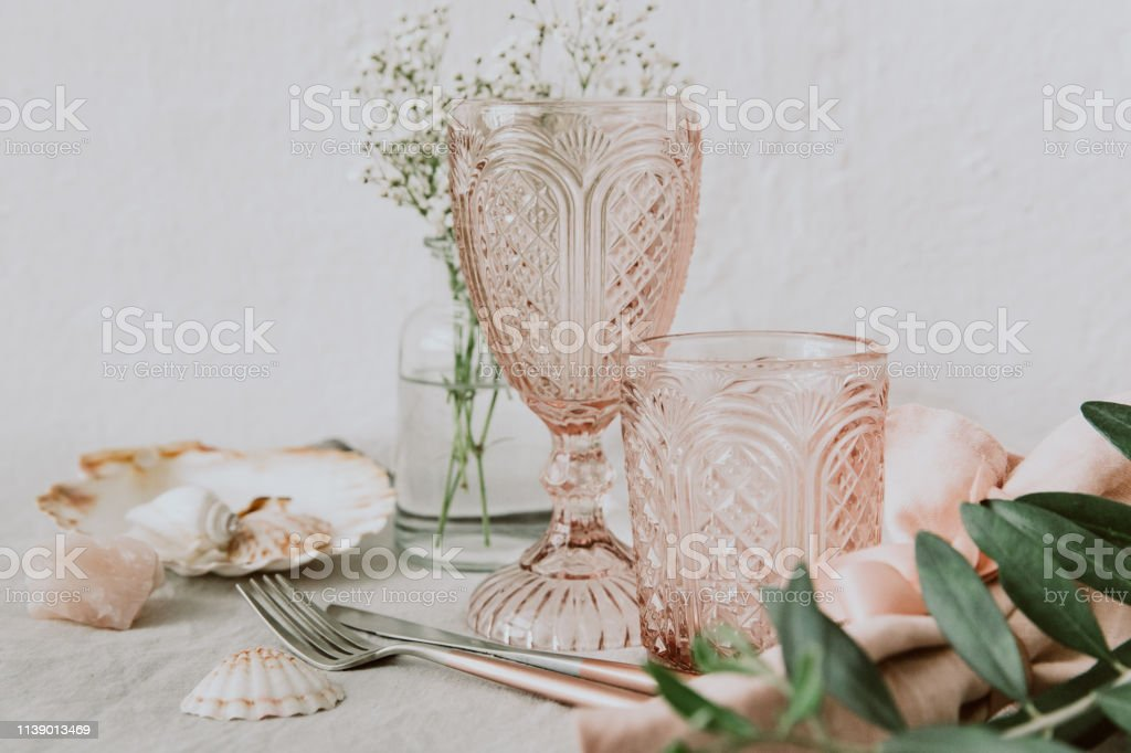 Pink Vintage Wedding Table Setting -crystal wine glasses with flowers, minimal lifestyle concept stock photo