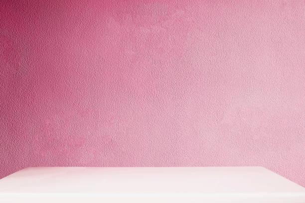 pared rosada y mesa blanca - foto de stock