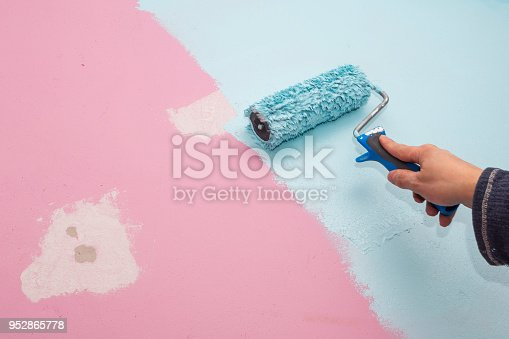 istock Pink wall of baby room is painted blue with hand and roller 952865778
