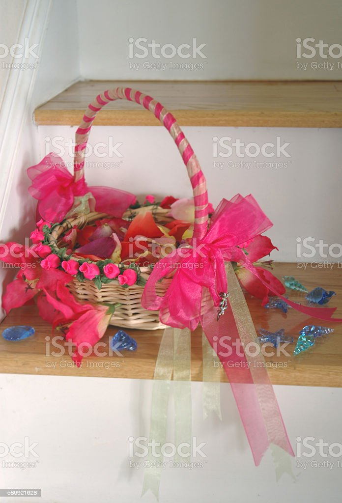 Pink wedding flower girl basket with red petals stock photo