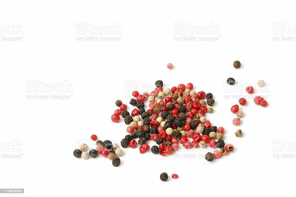 Pink, white and black peppercorns scattered on a white background stock photo
