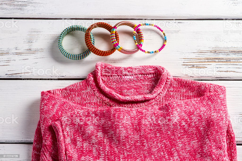 Pink wool pullover and bracelets. stock photo