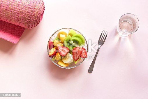 Feminine Sport and Healthy Lifestyle Concept. Pink yoga mat and Fruit and Berries Salad in bowl for snack or breakfast on pink pastel background, copy space.