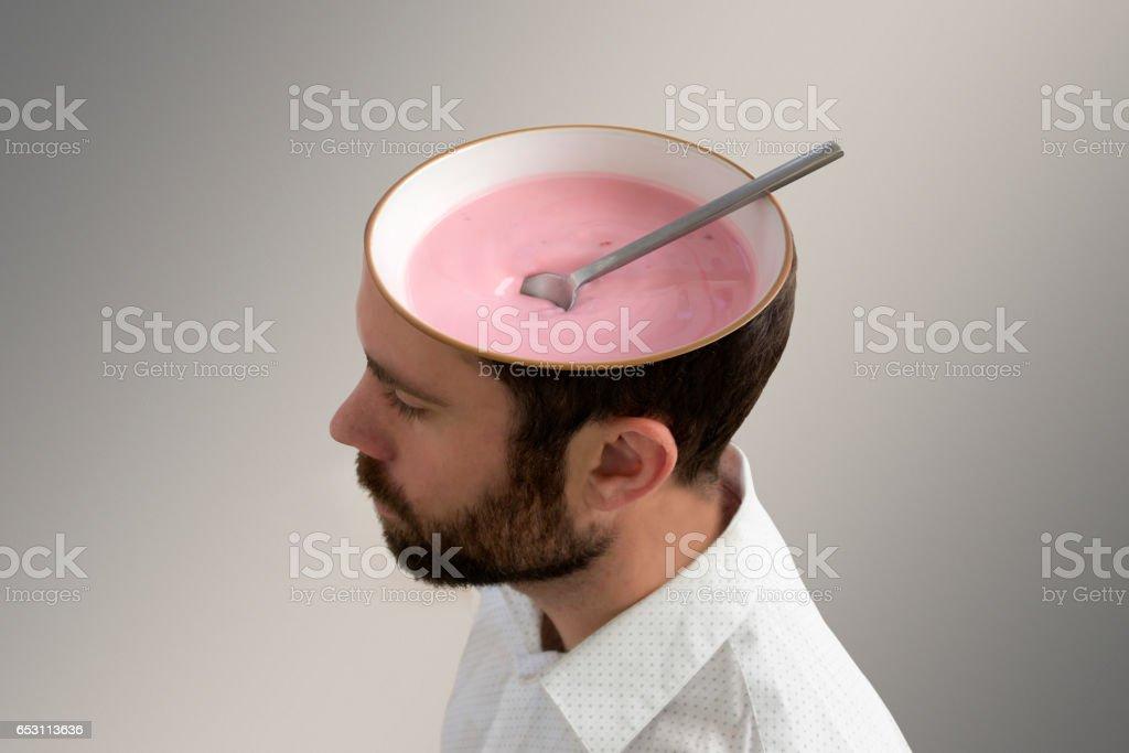 Pink yogurt inside a man's head. stock photo