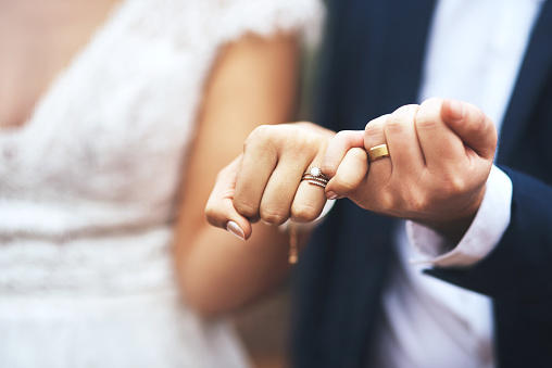 Cropped shot of an unrecognizable newlywed couple doing a pinky swear gesture on their wedding day