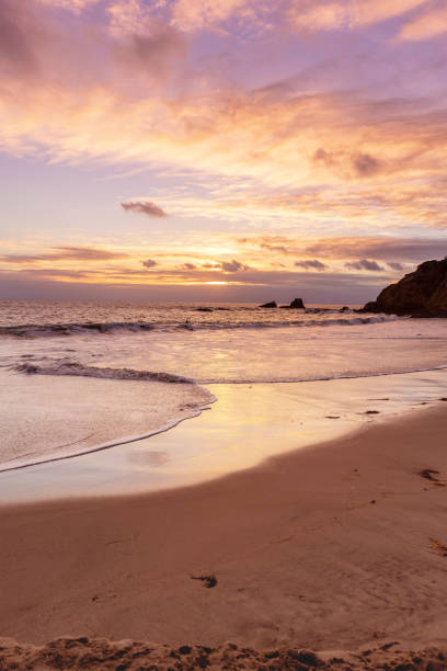 Pinky sunset at the beach with crazy sky and reflections on a wet sand. stock photo