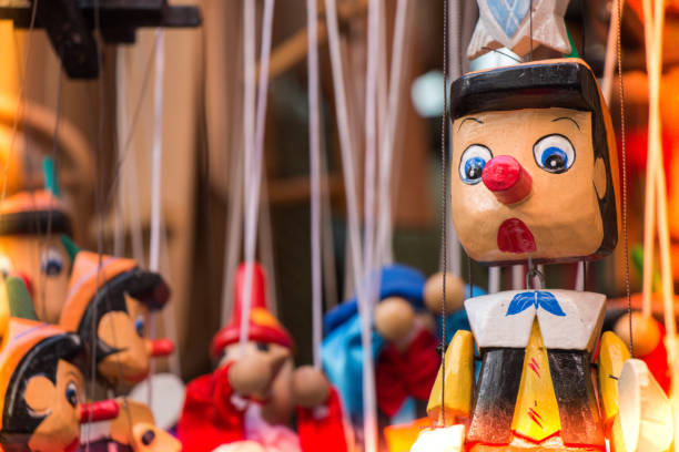 Pinocchio dolls with long nose. Conceptual fairy tale character. stock photo