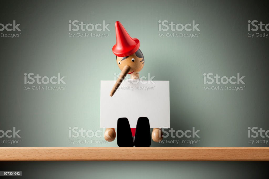 Pinocchio holding sheet of paper stock photo
