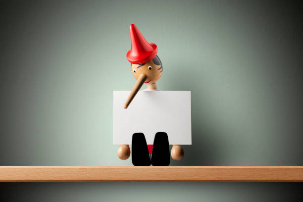 Pinocchio holding sheet of paper Pinocchio holding sheet of paper. pinocchio stock pictures, royalty-free photos & images
