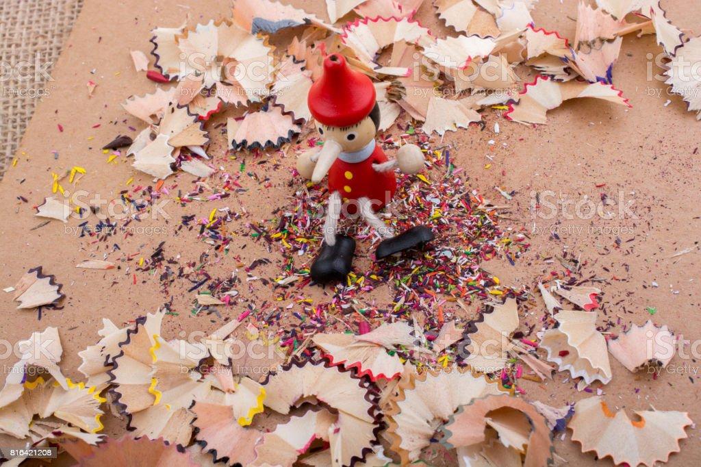 Pinocchio sitting amid pencil shavings stock photo