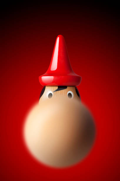 Pinocchio with a long nose in the foreground Pinocchio on red background. pinocchio stock pictures, royalty-free photos & images