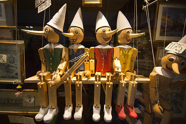 Pinochio Marionettes Venice, Italy - April 10, 2015: Pinochio puppets in a shop window display in Venice. Theer are four sitting in a symmetrical way with another in the bottom right including prices. pinocchio stock pictures, royalty-free photos & images