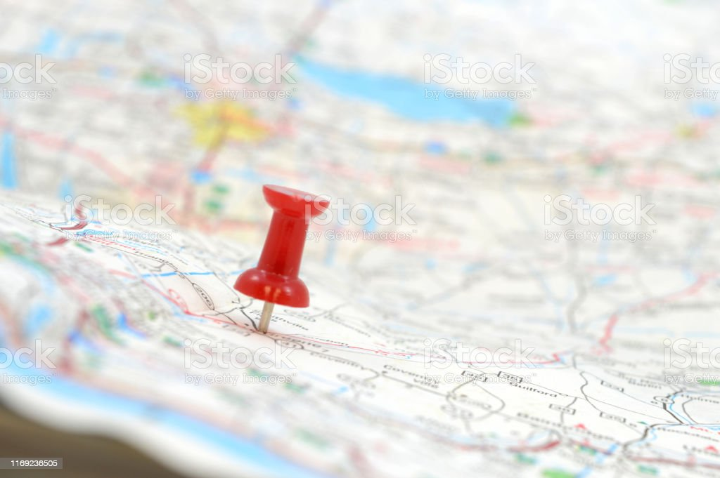 Pinpoint Mapped Destination A traveler has used a red pushpin to position the mapped out destination, shallow dof with the focus on the red tack. Aiming Stock Photo