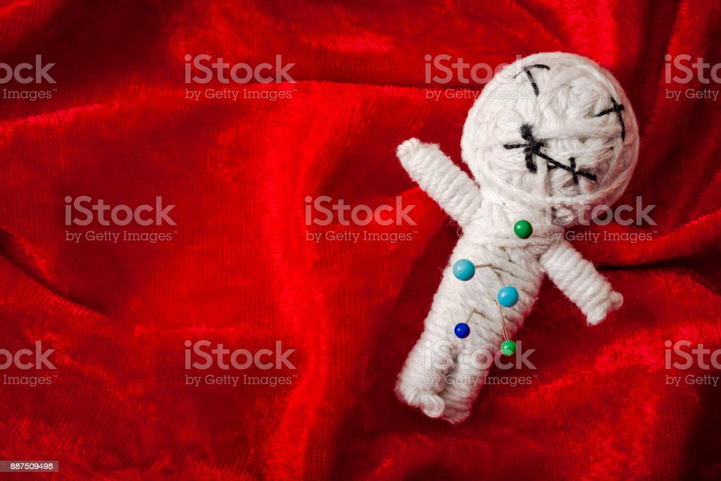 Pins in a Voodoo doll on red velvet with copyspace stock photo