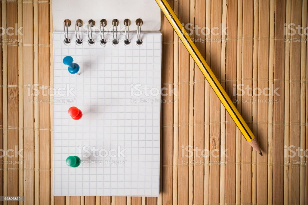 Pins, notepad and pencil on a bamboo table stock photo
