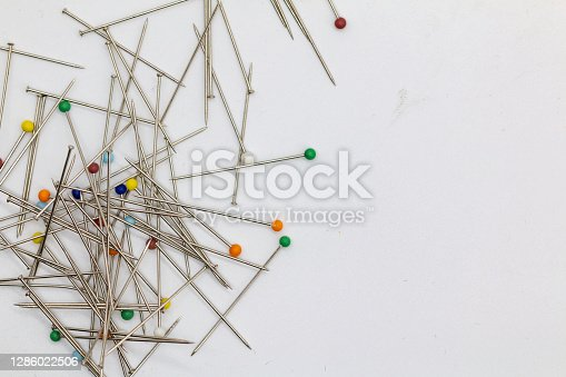 pins with colored heads on the white floor