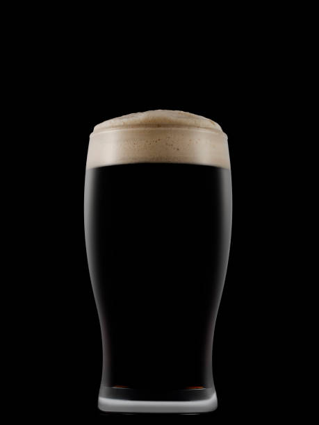 pint glass full of dark beer on a dark background - dark beer stock photos and pictures