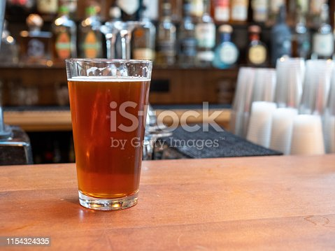 istock Pint glass of beer sitting on bar counter in the day time 1154324335