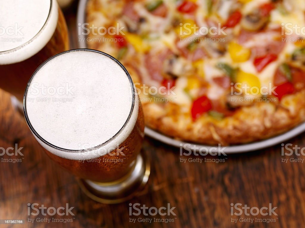 Pint of Beer and a Deluxe Pizza royalty-free stock photo
