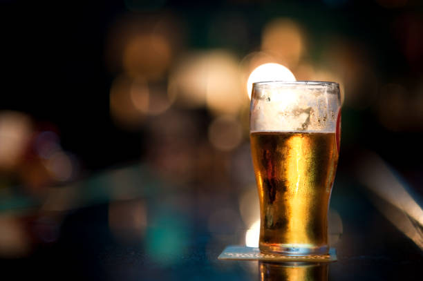 pinte de bière au bar - moitié plein photos et images de collection