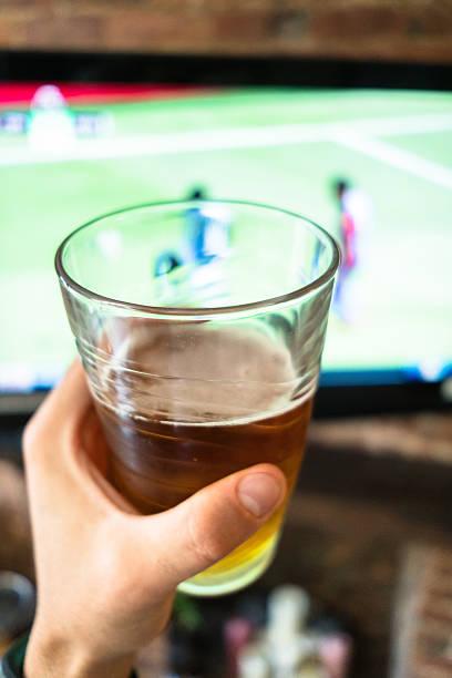 pint of beer on the living room watching a match - beer pov tv - fotografias e filmes do acervo
