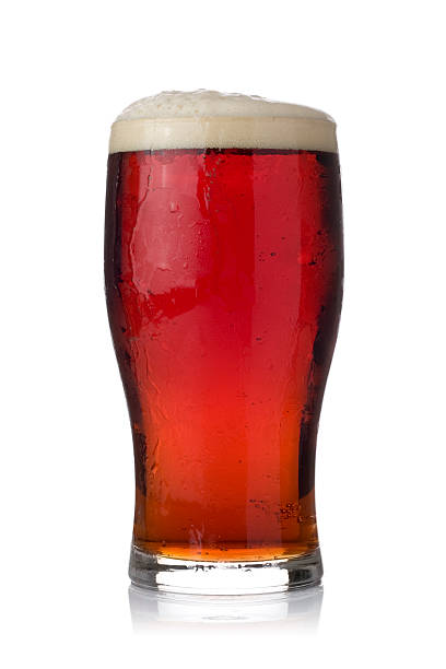 pint of dark ale on a white background - dark beer stock photos and pictures
