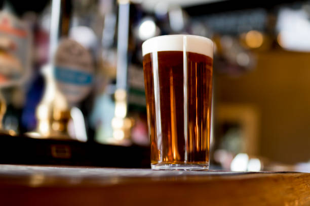 pint of real ale on the bar in a traditional english pub - dark beer stock photos and pictures