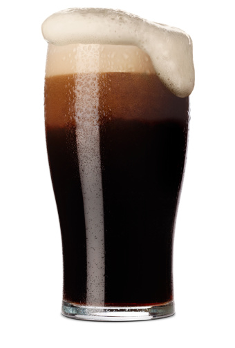 Freshly pulled pint of Stout with its frothy head in a traditional pint glass. Isolated on white with a small shadow