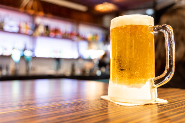 Pint of very cold and refreshing beer with pub background stock photo