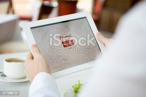 Moscow, Russia - August 9, 2013: Man hands holding iPad with Pinterest app. Pinterest is a pinboard-style photo sharing website that allows users to create and manage theme-based image collections such as events, interests, hobbies, and more.
