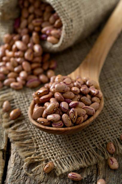 pinto beans on wooden surface - fasola pinto zdjęcia i obrazy z banku zdjęć