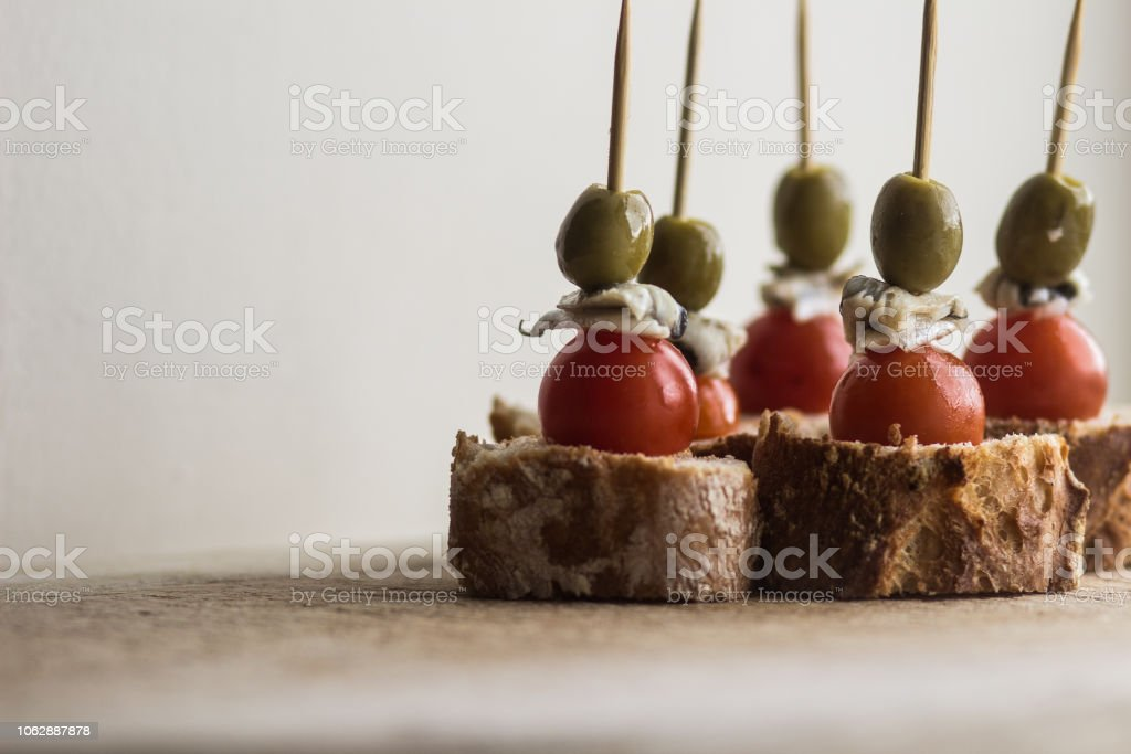 Pintxo with Olive, Anchovy, gilda pepper on Bread stock photo
