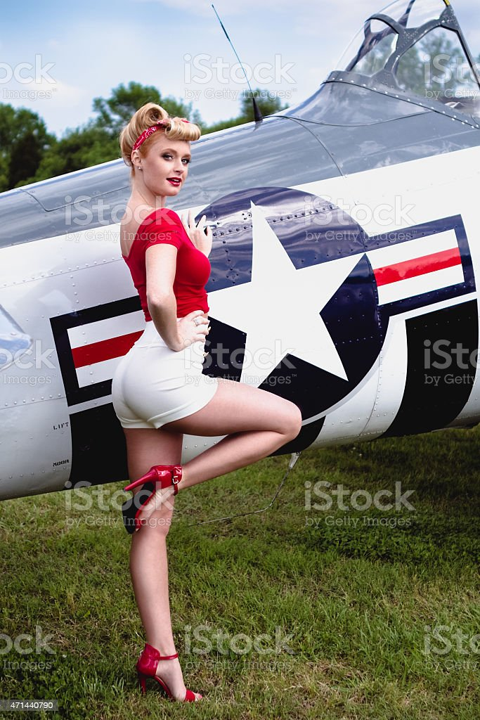 Pinup girl in red shirt leaning against WWII airplane stock photo