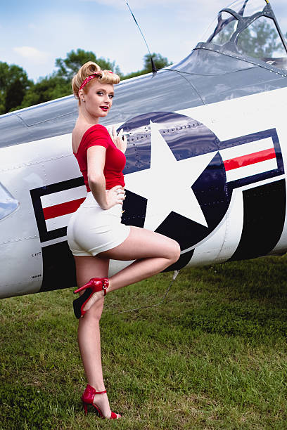 pinup girl in red shirt leaning against wwii airplane - airshow stock photos and pictures