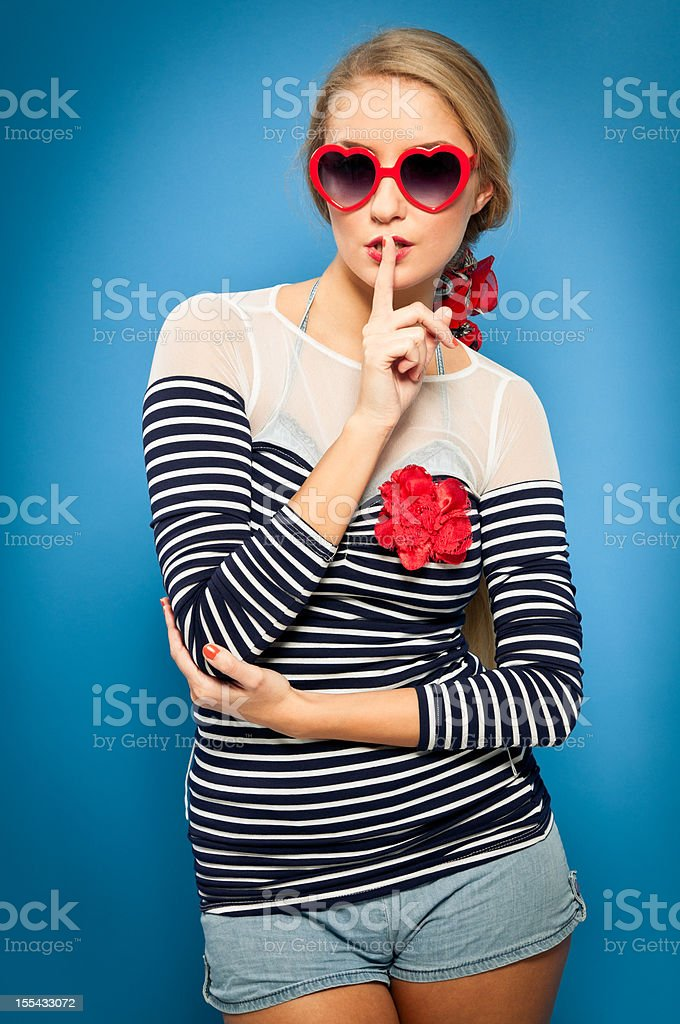 Pin-up girl, sailor outfit, heart shaped sunglasses, finger on lips royalty-free stock photo