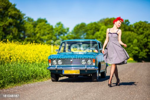 Beautiful young woman posing with old Polish (Italian) car in rural scenery.