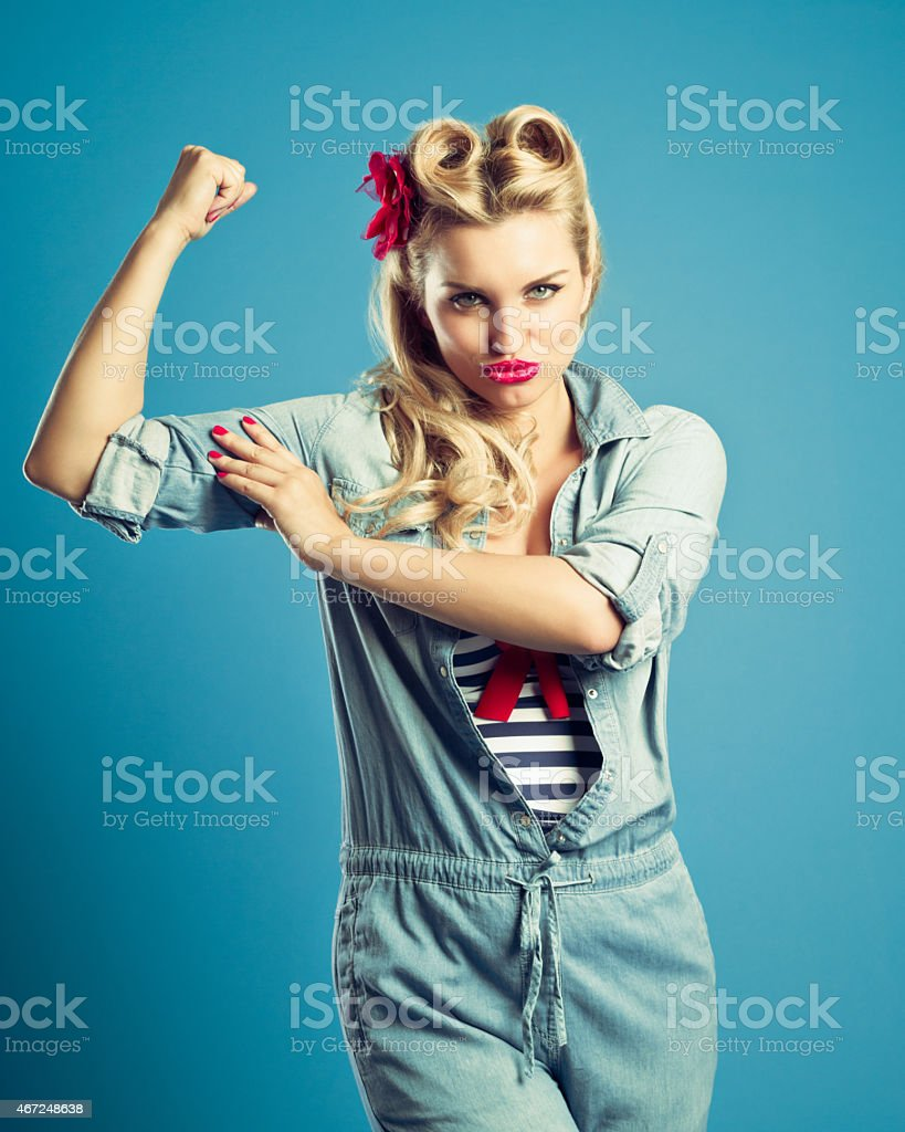 Pin-up style blonde woman flexing her arm stock photo