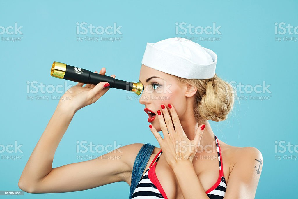 Pin-up style of sailor woman with telescope Young Blond Woman Wearing Striped Bikini and Blue Overalls looking through telescope. Standing against blue background and seems to be very surprised. Pin-Up style. Summer portrait. 20-24 Years Stock Photo