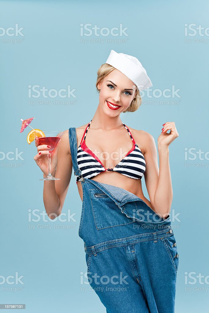 Pin-up style sailor woman holding a tropical cocktail Young Blond Woman Wearing Striped Bikini and Blue Overalls holding a tropical cocktail. Standing against blue background. Pin-Up style. Summer portrait. 20-24 Years Stock Photo