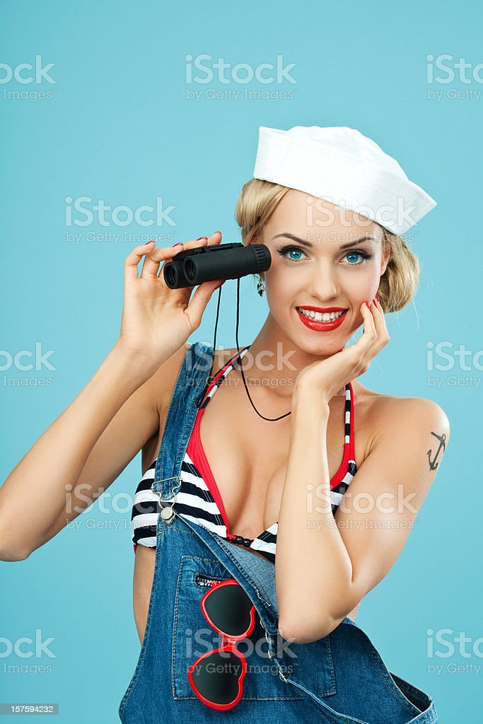 Pin-up style sailor woman holding binoculars in hand. Young Blond Woman Wearing Striped Bikini and Blue Overalls holding binoculars in hand. Standing against blue background. Pin-Up style. Summer portrait. 20-24 Years Stock Photo