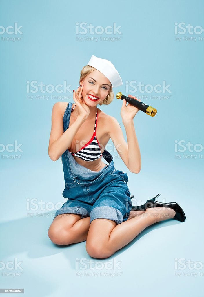 Pin-up style sailor woman holding telescope and smiling Young Blond Woman Wearing Striped Bikini and Blue Overalls holding telescope in hand and smiling. Sitting against blue background. Pin-Up style. Summer portrait. 20-24 Years Stock Photo
