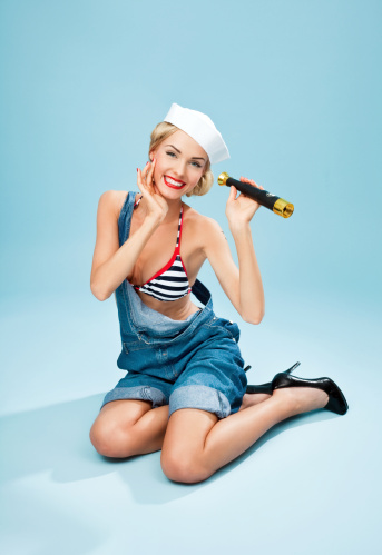 Pinup Style Sailor Woman Holding Telescope And Smiling Stock Photo - Download Image Now