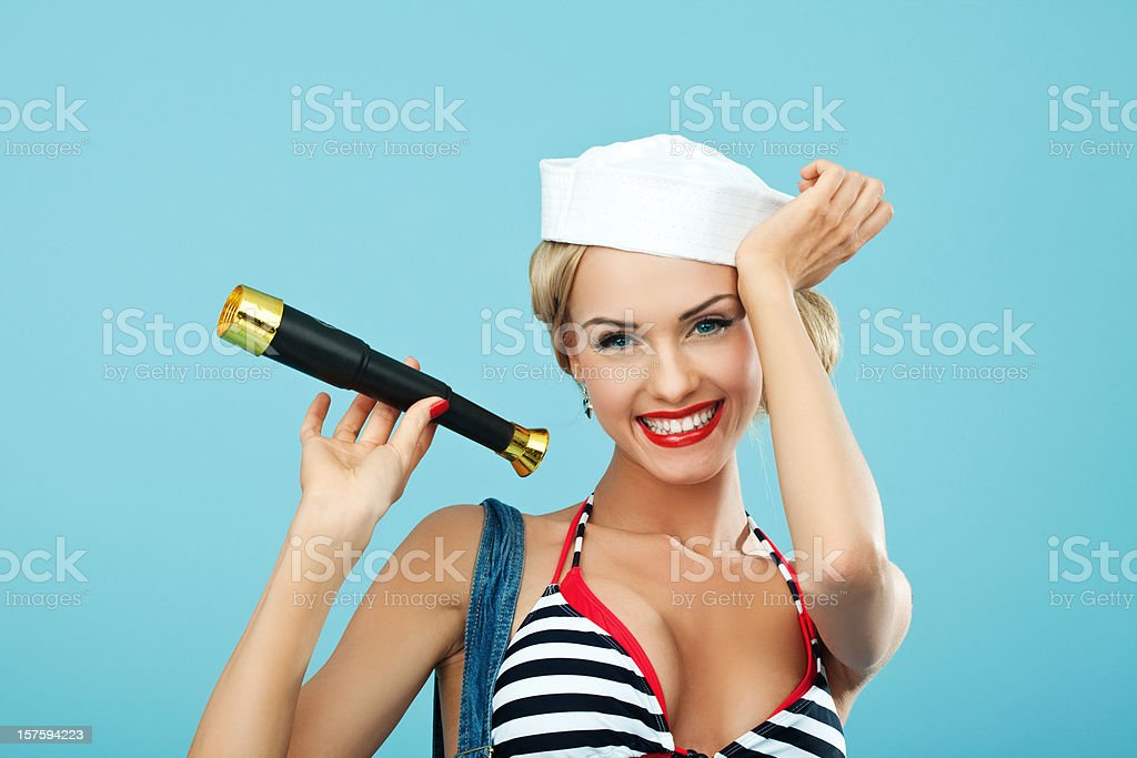 Pin-up style sailor woman holding telescope and smiling Young Blond Woman Wearing Striped Bikini and Blue Overalls holding telescope in hand and smiling. Standing against blue background. Pin-Up style. Summer portrait. 20-24 Years Stock Photo