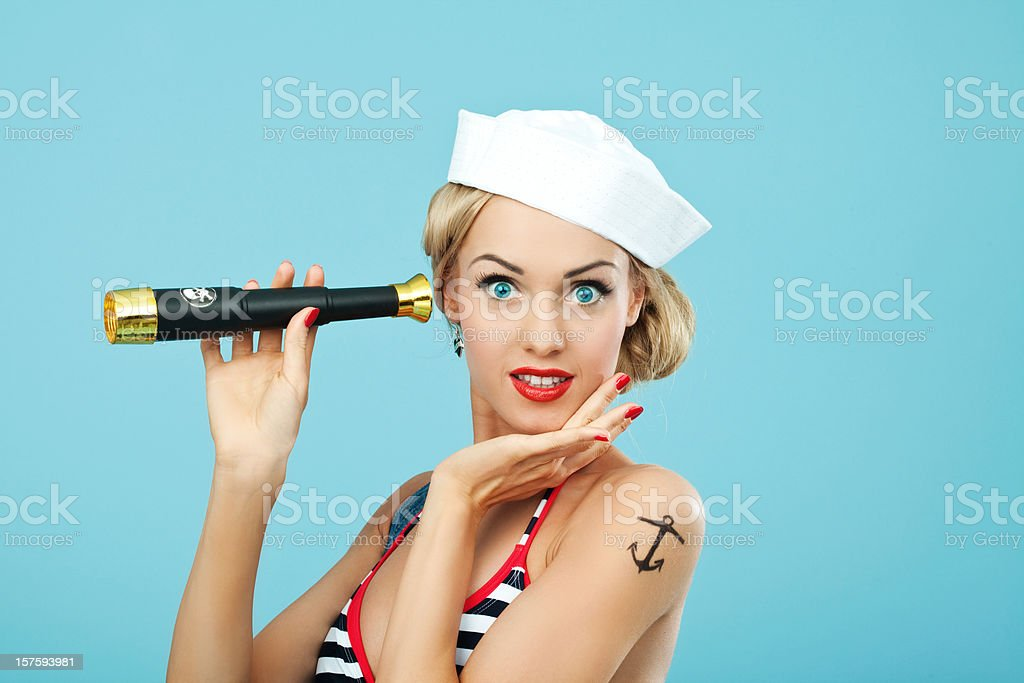 Pin-up style sailor woman holding telescope Young Blond Woman with anchor tatoo on her arms Wearing Striped Bikini and Blue Overalls holding telescope in hand. Standing against blue background. Pin-Up style. Summer portrait. 20-24 Years Stock Photo